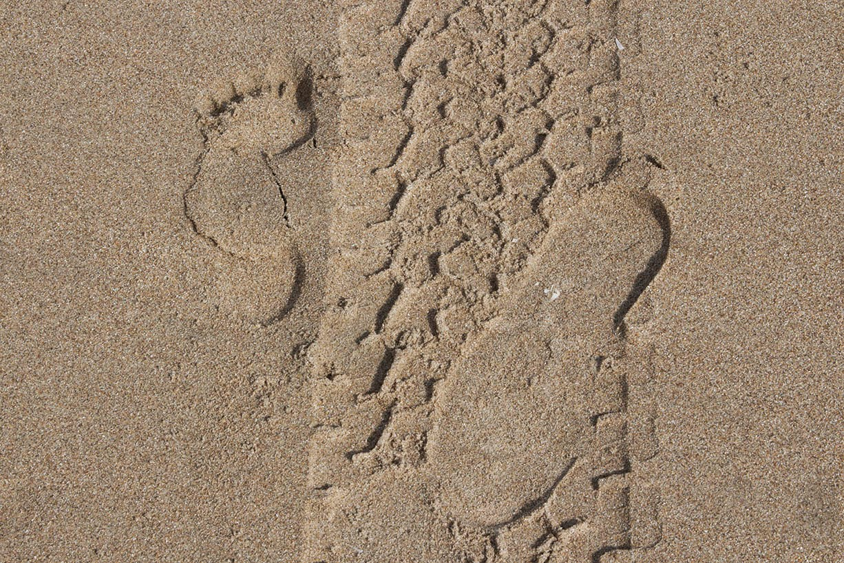 two footsteps and tyre track in sand