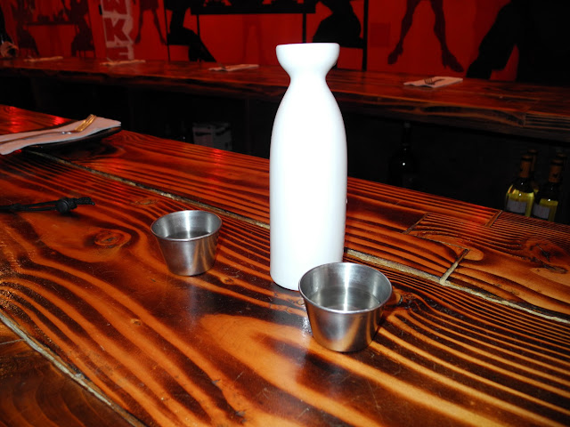 Small porcelain jar of warm sake and two metal shot cups