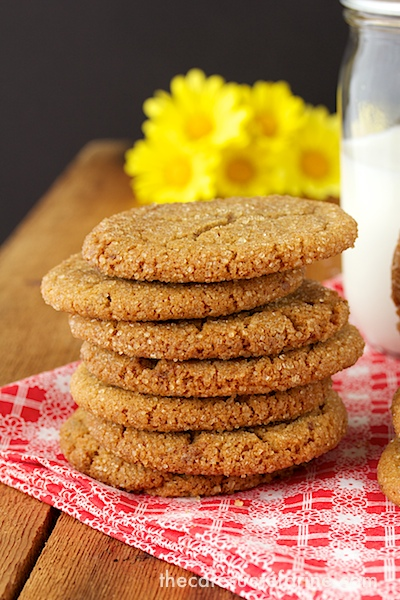 A photo of a stack of Biscoff Toffee Cookies on a red and white napkin on a wood table with a jar of milk and yellow daisies in the background.