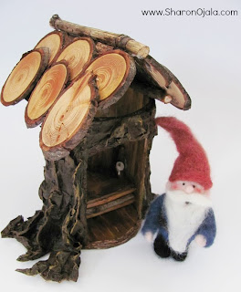 felted gnome standing beside outhouse