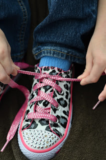 learning to tie shoes, pulling the half tied laces tight