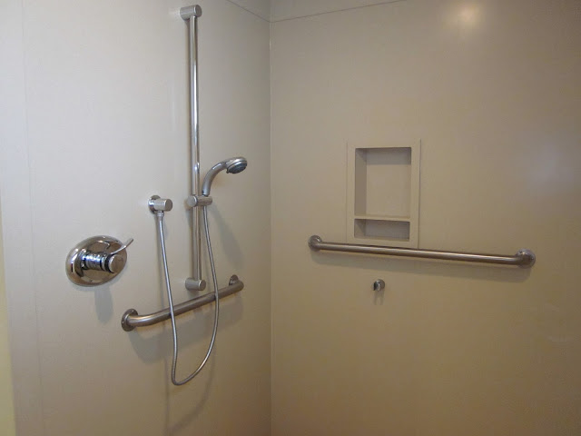 a stainless steel bathroom safety bars in the white wall