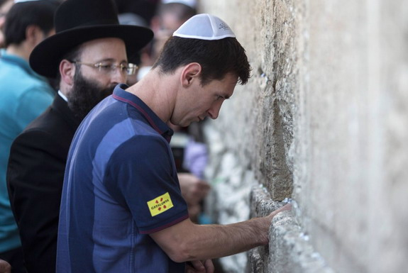 Barcelona player Lionel Messi puts a paper with wishes in a crack of the Western Wall