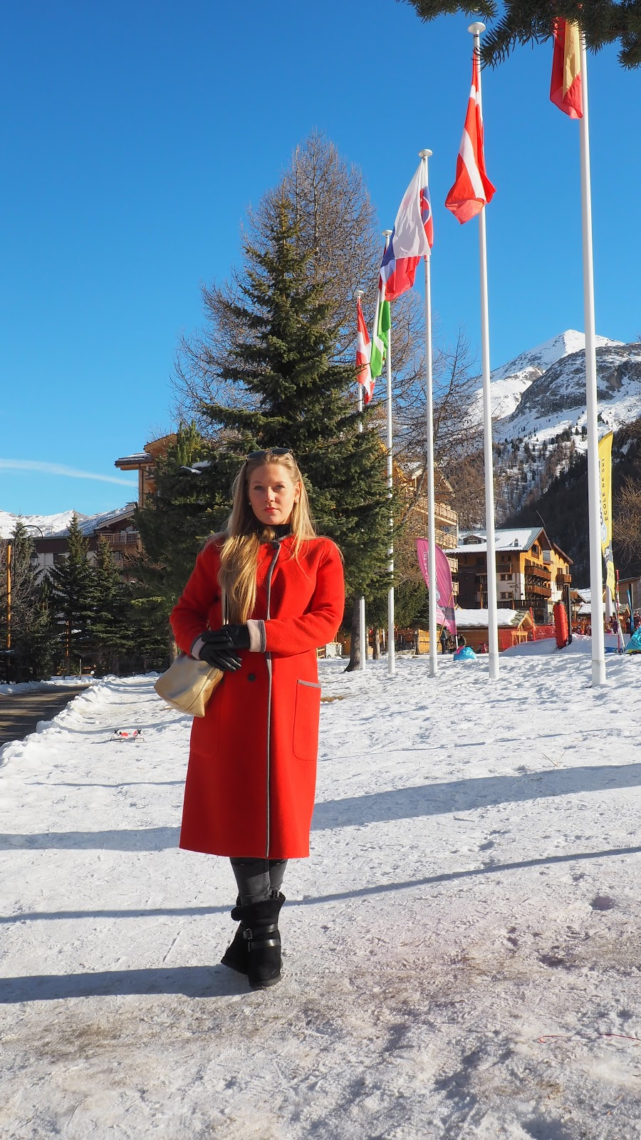 Blonde Girl wearing red coat in the snow, Val d'Isere, France