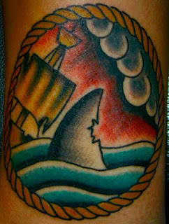 Tattoo of a bitten shark fin swimming towards an old wooden ship framed by a circle of rope by Tattoo artist Mark Stewart for Triumph Tattoo