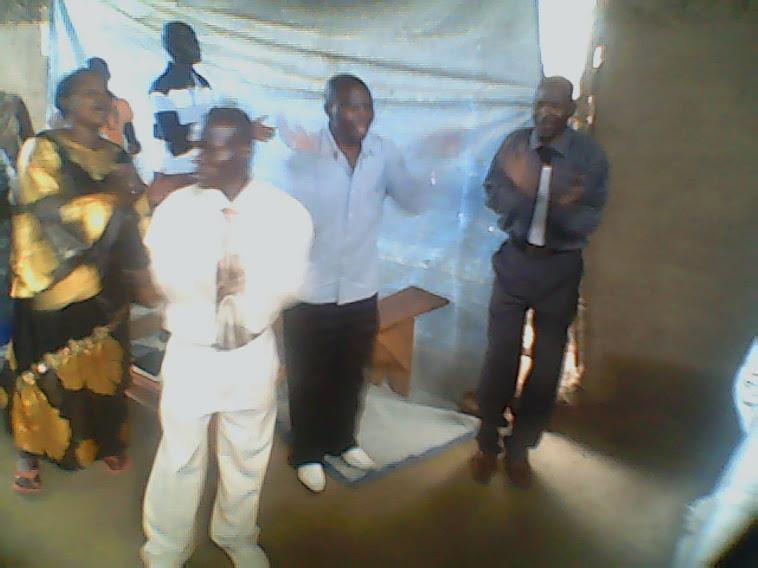 PASTOR JOHN & PASTOR BEN IN PRAYER WORSHIPING THE LORD WITH PASTOR SAM FAR RIGHT.