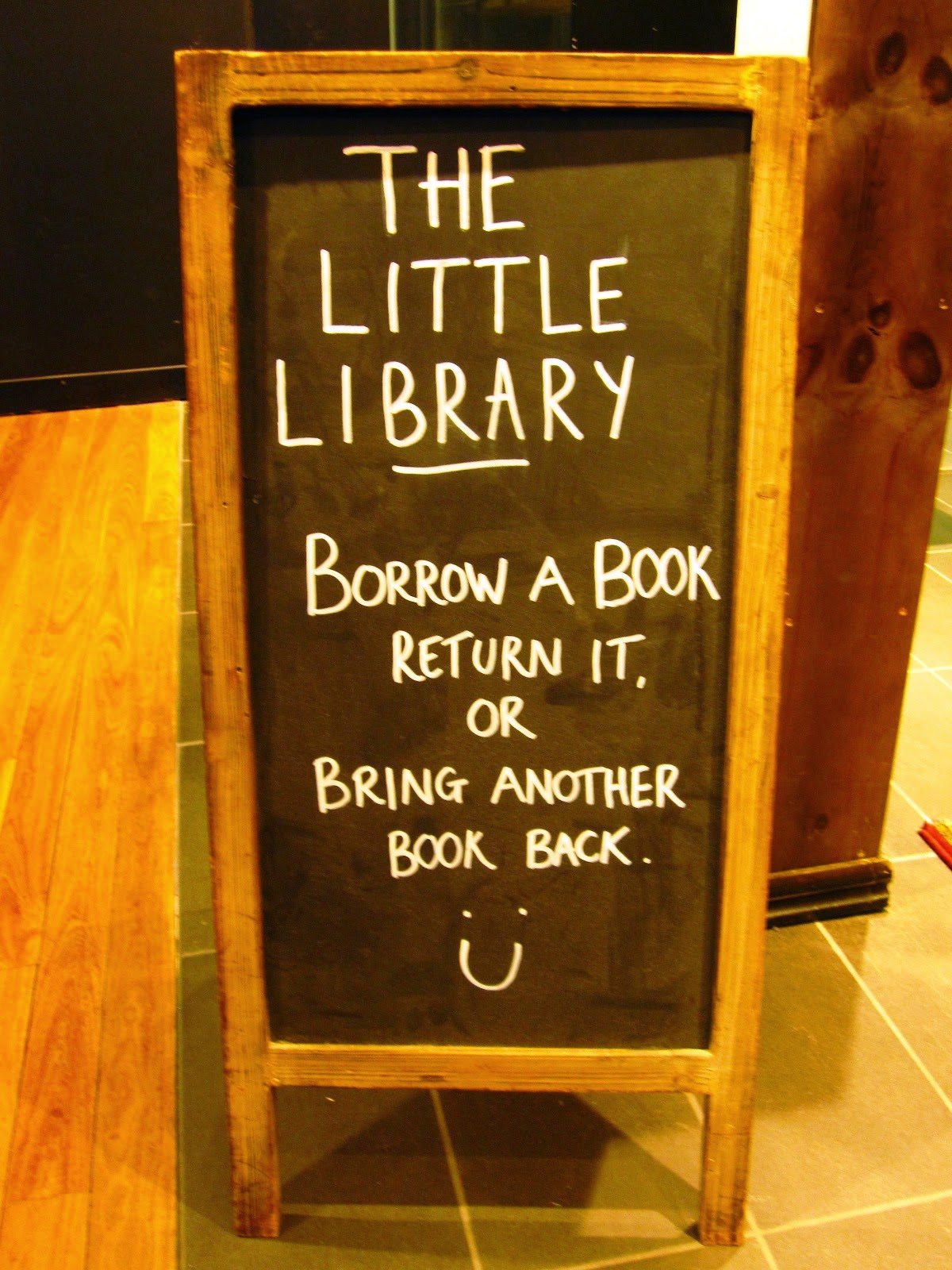The Little Library in Melbourne Central: blackboard instruction sign saying 'Borrow a book return it. Or bring another book back.'