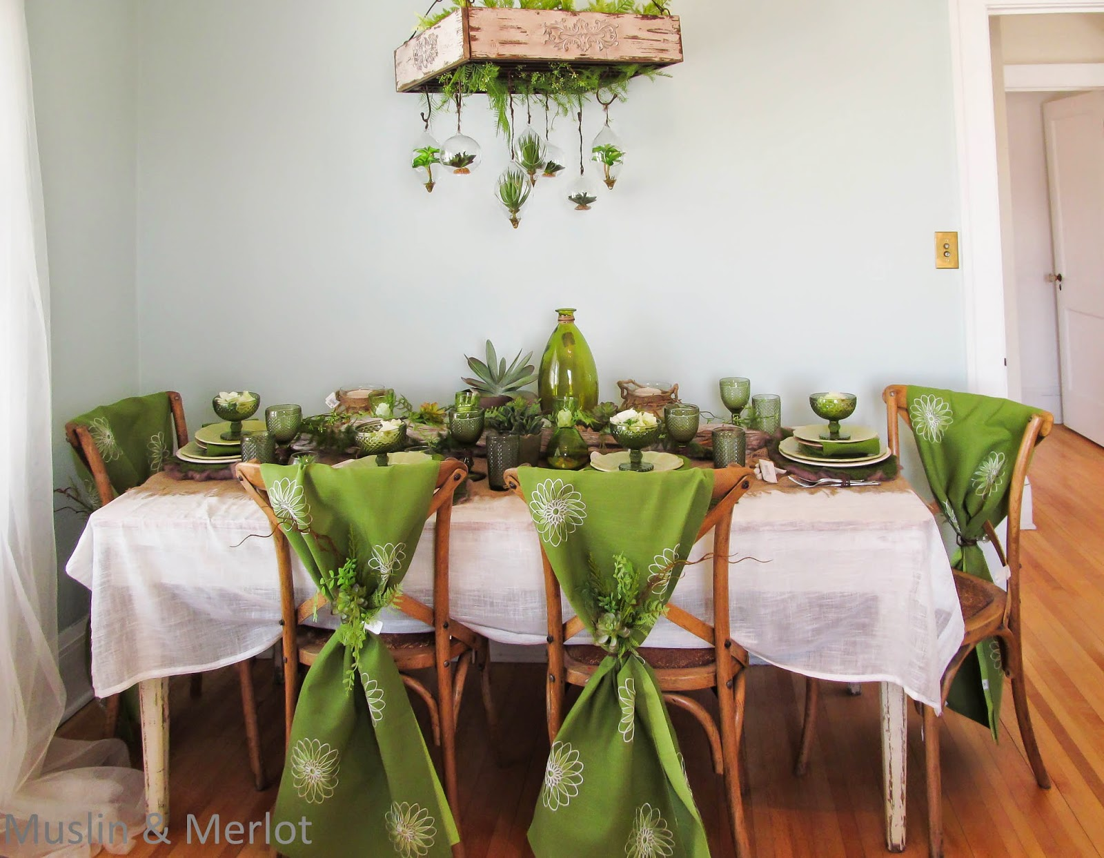 Table runners used as chair covers. Green moss place mats. Centerpiece of salvaged driftwood, succulents, rock and grass.
