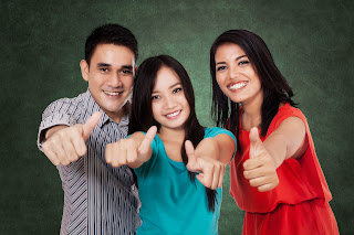 Three Hispanic students give thumbs up.