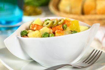 Spaanse aardappelsalade met zelf gemaakte mayonaise van olijfolie en citroensap, geserveerd met gekookte wortelen en erwten