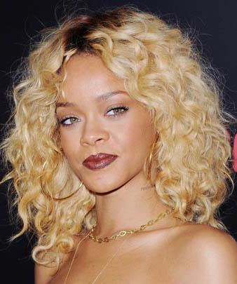 Rihanna'nın çılgın olduğunu anlayabilmemiz için sadece çılgın saç renklerine ve çılgın saç kesim modellerine gerek yoktur. Zenci olmasına rağmen açık sarı saç rengine cesaret edebilmesi Rihanna'nın oldukça çılgın olduğunu göstermeye yeterli bir sebeptir. Pekala Rihanna sarı saç rengi ile yanlış bir tercih mi yapmıştır? Asla! Bu soruya hiçkimsenin evet yanıtını veremeyeceğinin farkındayım. Çünkü Rihanna sarı saçları ile Barbie bebek gibi görünmektedir. Esasen bu görünümünün en büyük sebeplerinden biri de onun bebeksi yüz hatlarına sahip olmasındandır. Rihanna sarı saçlarına kıvırcık saç modeli yaptırarak bu sempatik görünümü bir kat daha arttırmış ve yine güzelliği ile göz kamaştırmıştır.