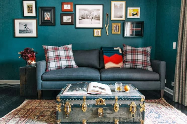 Teal living room with red, white and green Tartan pillows and a trunk with gold detailing doubling as a coffee table
