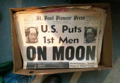 Photo of a box holding a copy of the St Paul Pioneer Press from July 1969 with huge headline U.S. Puts 1st Men ON MOON
