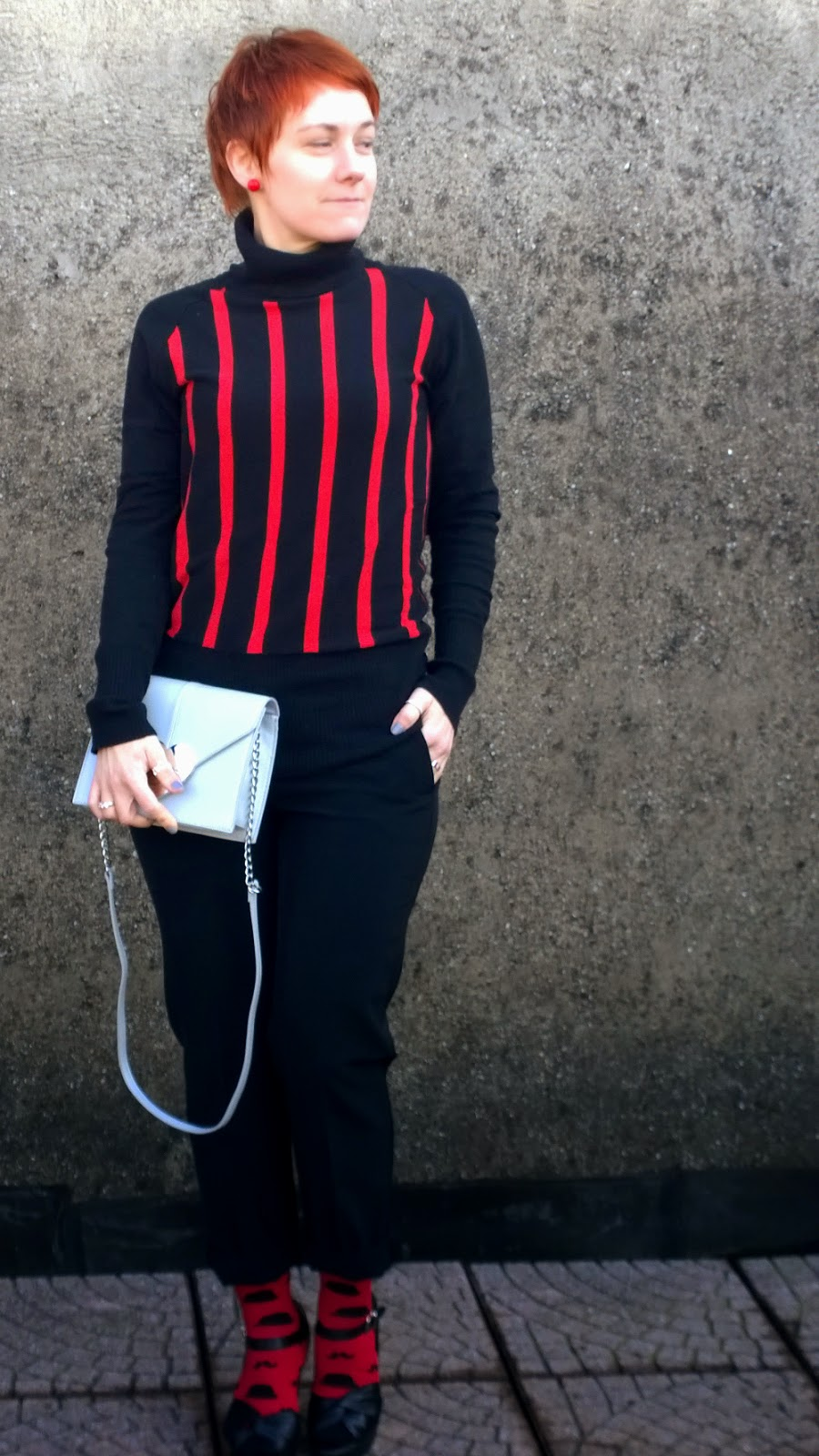 Wearing a black turtleneck with red stripes, black pants, red socks with mustaches, platform sandals and a grey heart closure bag