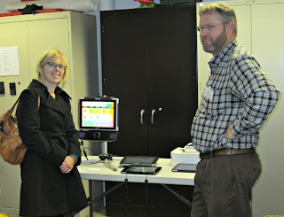 A participant looks at a devices from DynaVox.