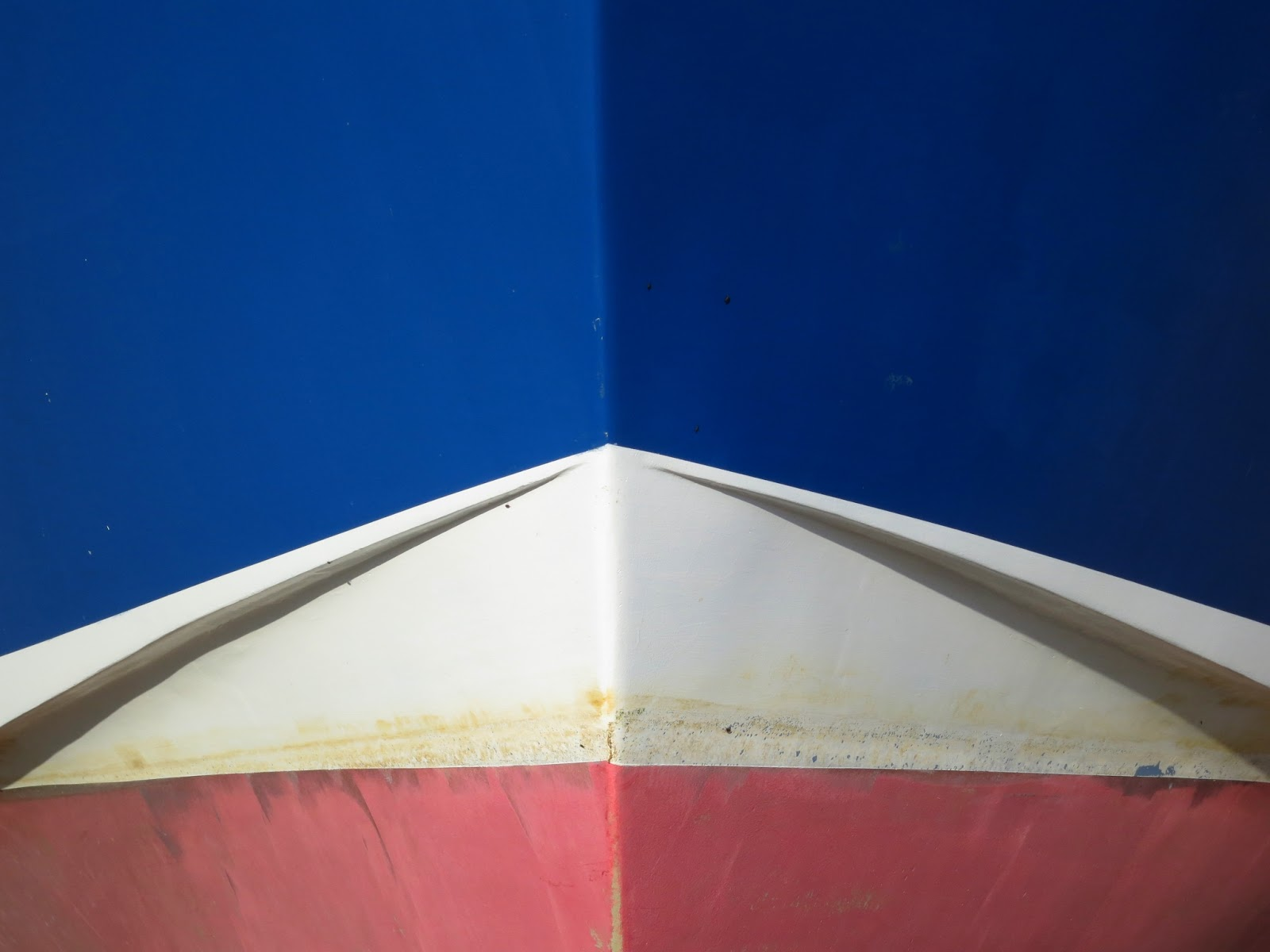 Red white and blue colours of boat removed from water.