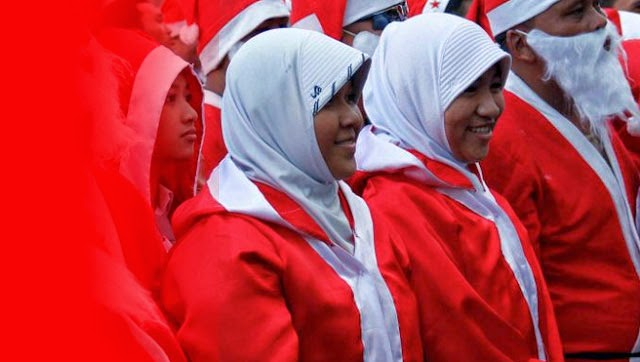 Haram hukumnya karyawan muslim mengenakan atribut Natal, seperti baju dan topi Sinterklas. Dalil keharamannya ada dua; pertama, karena mengenakan atribut Natal tersebut termasuk perbuatan menyerupai kaum kafir (tasyabbuh bil kuffar). Kedua, karena perbuatan tersebut merupakan bentuk partisipasi (musyarakah) muslim dalam hari raya kaum kafir yang sudah diharamkan dalam Syariah Islam.