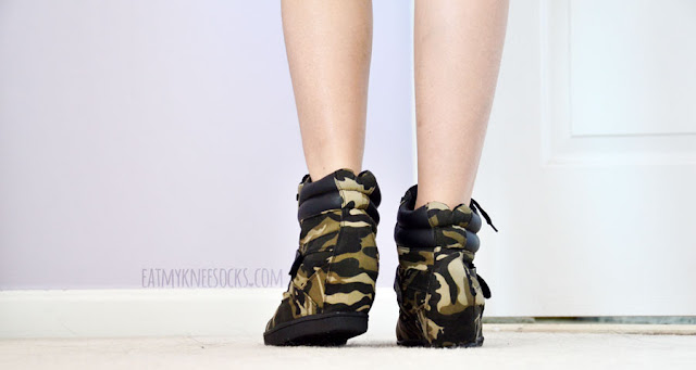 The camouflage-print canvas sneaker wedges from AMIClubwear feature black laces and a faux leather velcro strap embellishment.