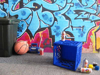 Modern dolls' house miniature street scene of a wall of street art with a milk crate and spray cans in front of it.