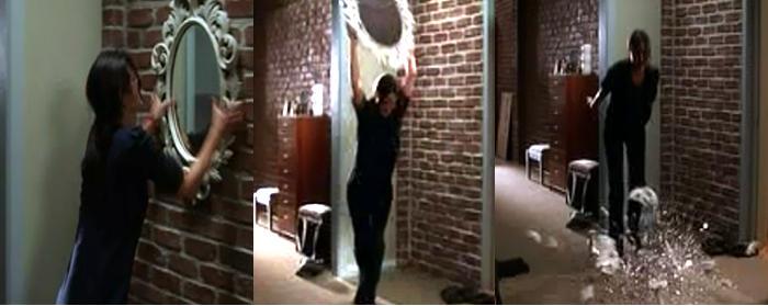 ira mujer enfadada rompiendo un espejo contra el suelo