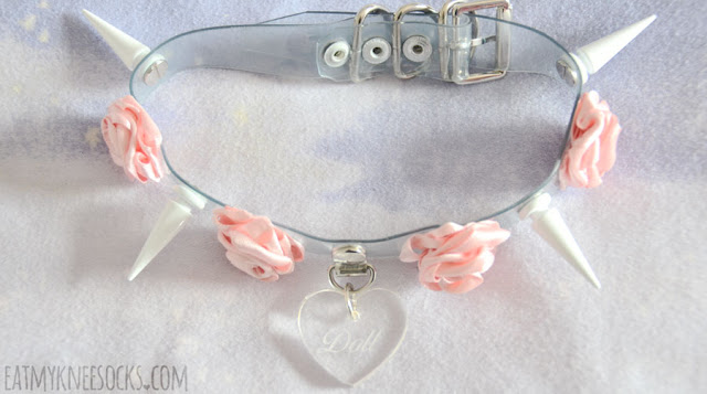 The clear babydoll choker from Milkstud looks exactly as pictured, with a dangling Doll-engraved heart-shaped pendant, pink 3D ribbon roses, and large white spikes.