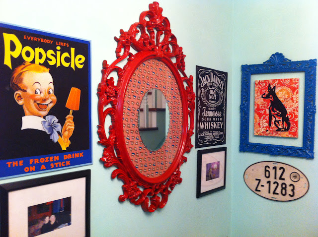 Cottage Home: vintage advertising tins, family pictures, a vintage license plate and a bold mirror for wall decor on BinkysNest.com