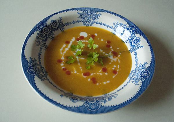 Tallrik med blomsterbård fylld med en slät, orange soppa.