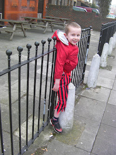 boy hanging off fence by coat
