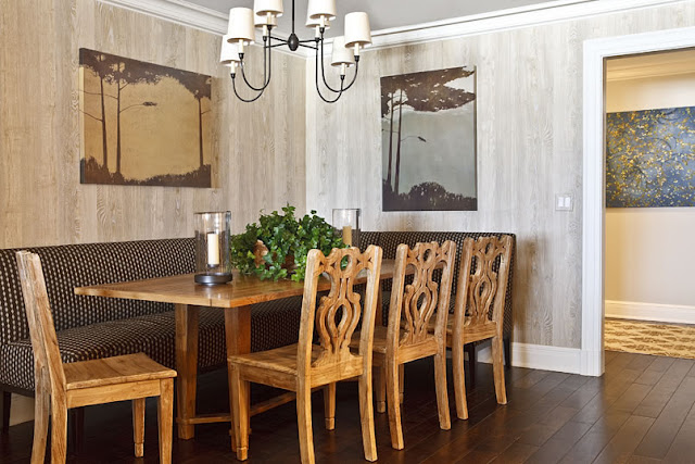 Dining room with grey stained wood walls, a wire chandelier, four carved wood chairs, a farmhouse style wood table and black and gold poka dot banquette seating 