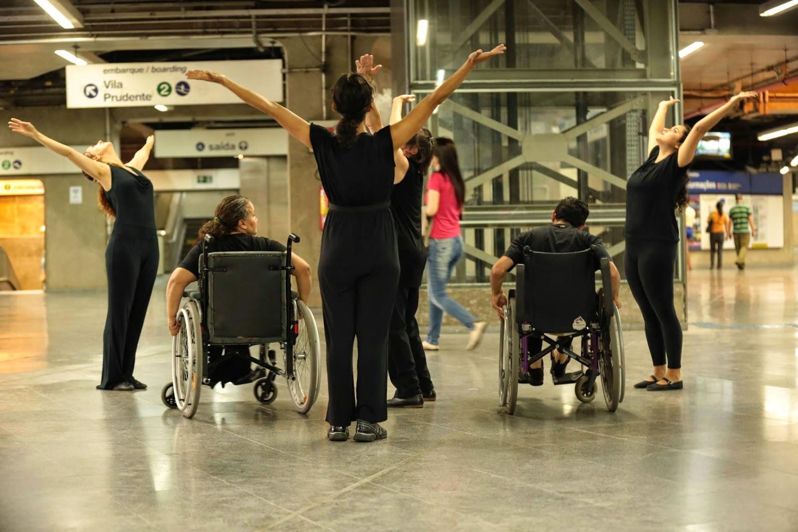 Seis intérpretes vestidos de preto dançam na plataforma do metrô. Dois deles estão numa cadeira-de-rodas. Quatro intérpretes estão de pé, rosto voltado para cima, braços abertos estendidos em V. São quatro pessoas de pé, um ao centro com dois cadeirantes de costas e, três envolta formando um triângulo. Pessoas passam, placas de sinalização no alto e elevador no fundo.