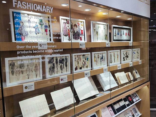fashion illustration framed on bookshelf behind glass