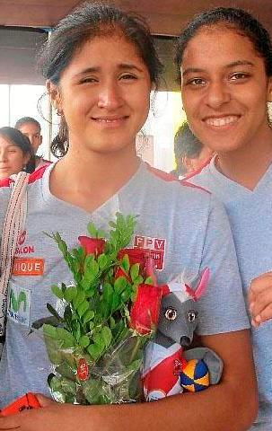 Vivian Baella con rosas y peluche junto a su amiga