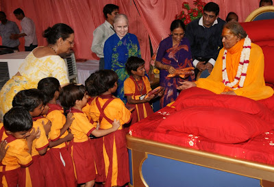 Jagadguru Kripaluji Maharaj giving uniforms to girl students