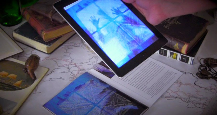 Showing the iPad interacting with the printed book, Ice-Bound Compenidum, in the IndieCade finalist Ice-Bound