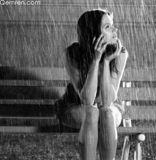 girl sitting on bench in rain