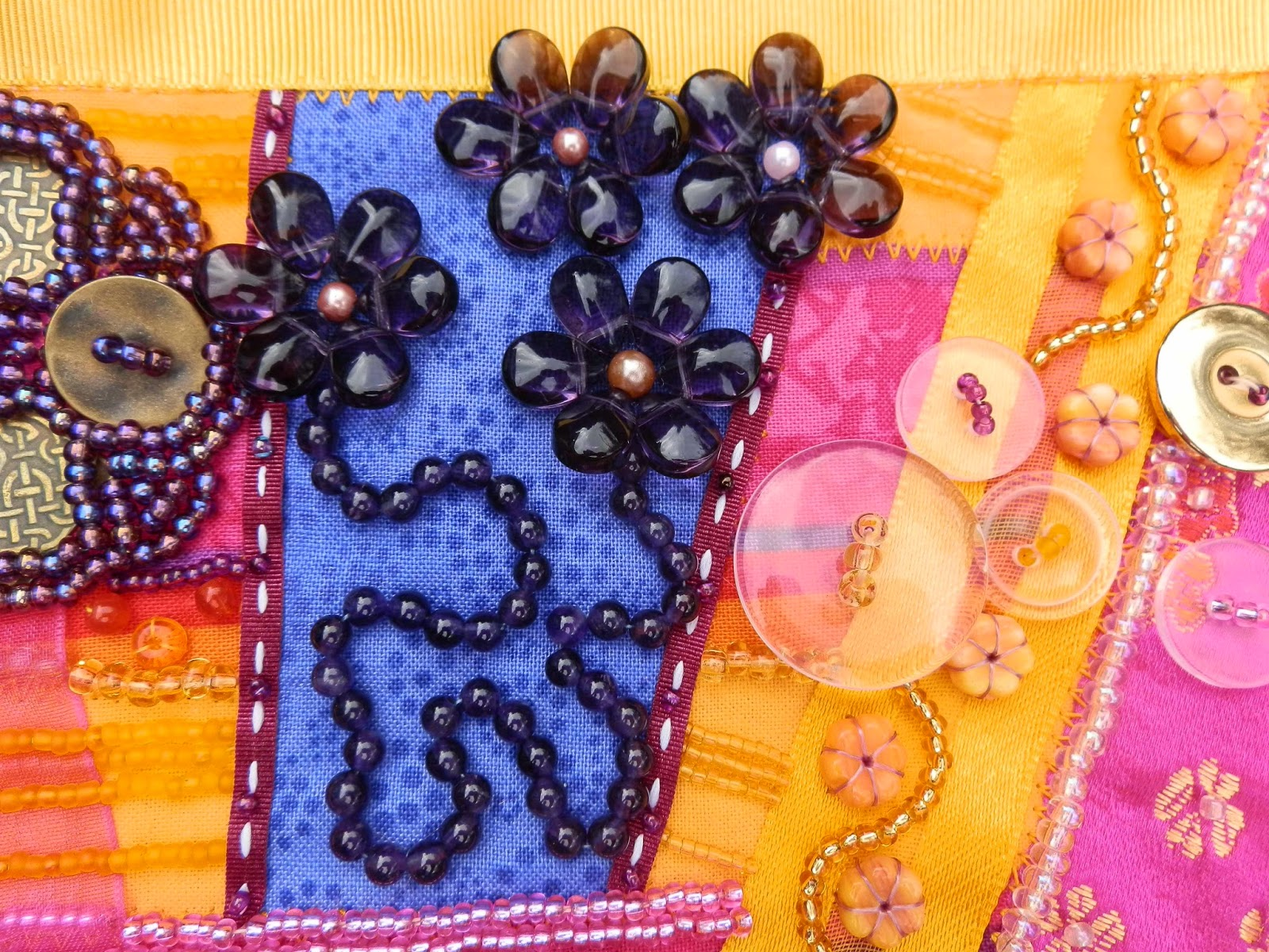 Detail showing purple beads shaped like flowers and clear beads