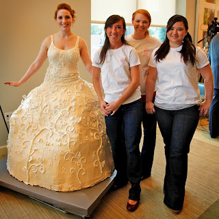 The bride poses with the dress makers