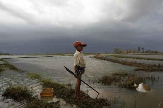 A boy whose house was destroyed by the cyclone watches an approaching storm