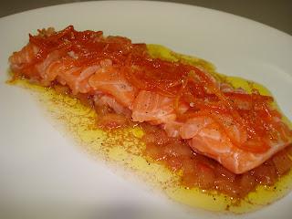Sashimi de salmón marinado sobre cama de tomate y naranja confitada