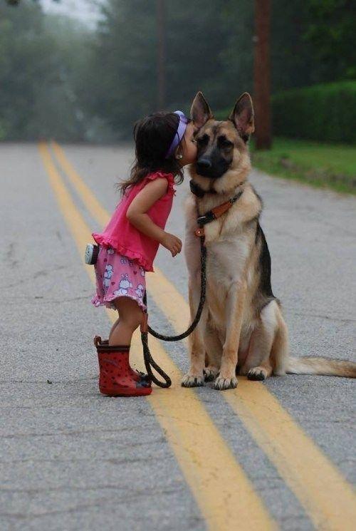 Little Girl Kissing Her Dog In The Street