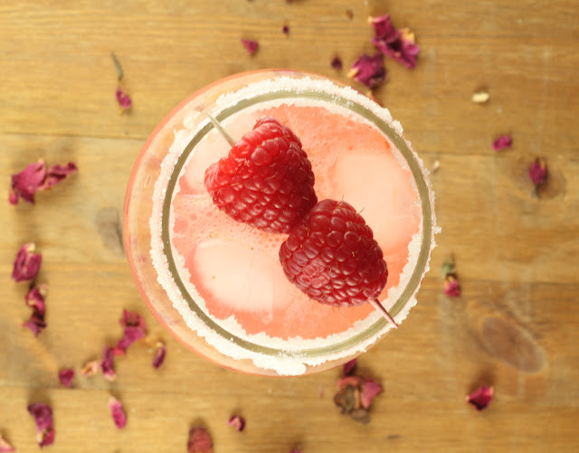 Overhead shot of Raspberry Rosewater Gin Rickey with raspberry garnish and dried rosepetals around the glass
