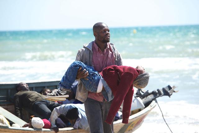 Vor einem schlichten Holzboot, in dem leblose Körper liegen, steht ein Mann, der einen kleinen Jungen in den Armen trägt. Hinter ihnen das offene, türkisfarbene Meer ...