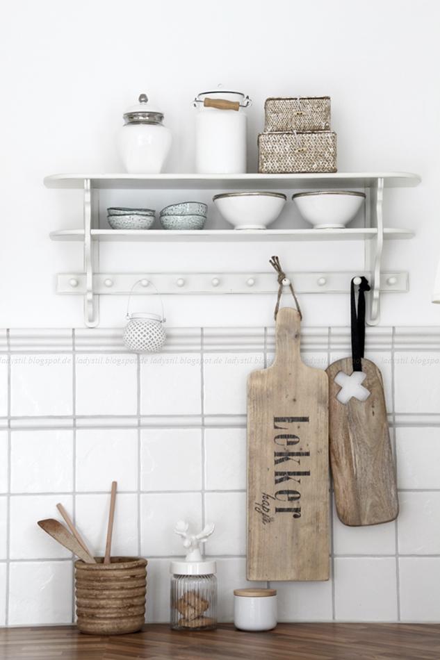 Küchenregal in weiß mit weißen Accessoires, es hängen große Holzbrettchen daran