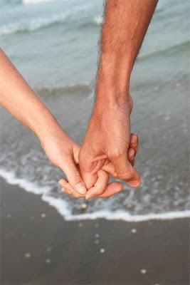 Must-Have Stages In A Relationship - two lovers holding hands on a beach
