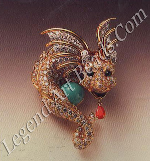 Below, a dragon brooch designed by Donald Claflin, with diamond pave body, emeralds, ruby, cabochon turquoise (1968).