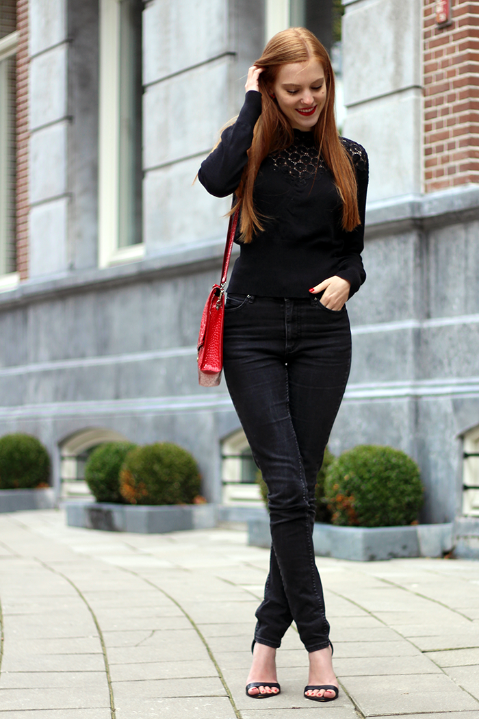All black fashion blogger outfit with a lace sweater, high waisted black jeans and pops of red