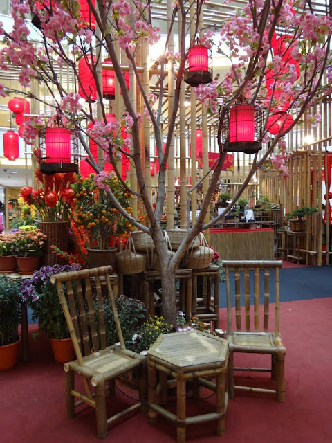Bamboo table and chairs with plastic Plum Blossoms and red lanterns at Mid Valley Mall in Kuala Lumpur, Malaysia