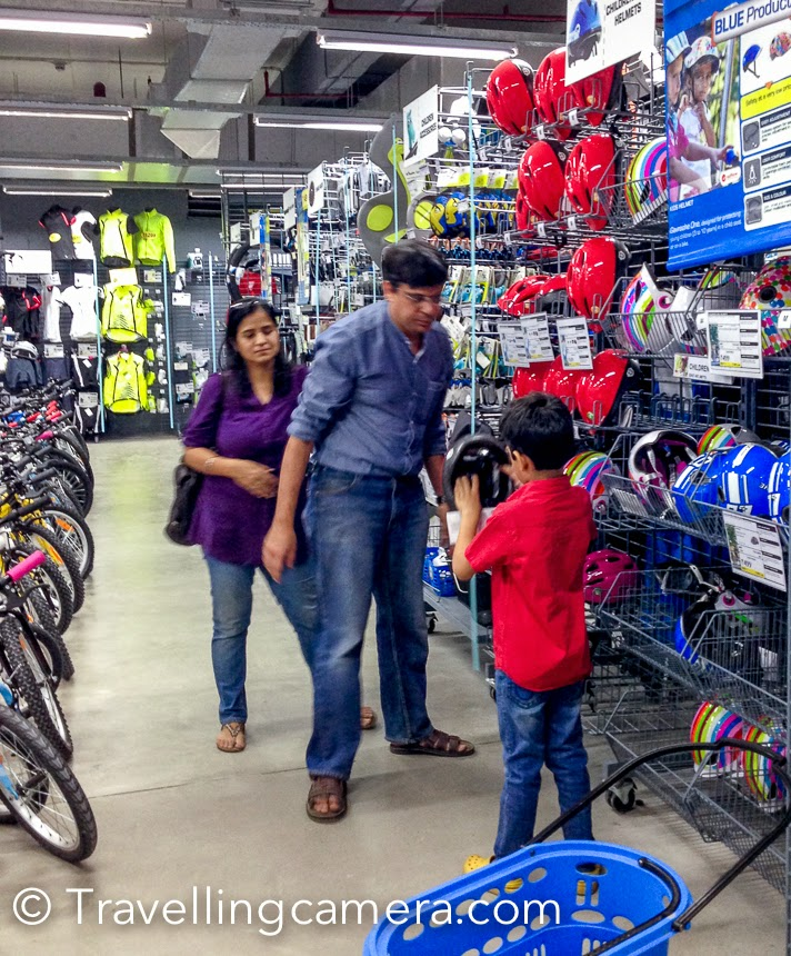 On a weekend in October, Nishant visited us in Noida with his parents and one of the main agenda was to visit Decathlon. This Photo Journey shares some photographs clicked with iPhone and more details about the place. Decathlon is near Great India Place Mall (GIP) in Noida. If you are going there in your own car, you can either park it in the covered parking of the mall or opt for easily available open parking near Decathlon. Anyways, you need not worry about pros and cons of parking inside the Mall or near Decathlon because there is frequent shuttle between GIP and Decathlon. The photograph above shows the toy-traint that runs between these two places and it's not only for kids, everyone can enjoy the ride :). We chose to park the car in GIP parking, did some shopping, and then headed towards Decathlon. We took the train from GIP to Decathlon. No tickets, it's FREE. Just wait for few minutes for the train and catch a comfortable ride to Decathlon. Overall it takes 5-7 minutes. Decathlon is a sports/outdoor mega store which caters to all imaginable requirements that a person interested in sports or outdoor activities can have. And that's why Nishant was there. We started looking at camping stuff, picked few basic utility articles which can be used during travel. Since it's a huge store, we started from one side and went sequentially to ensure that we don't miss anything :), although Nishant wanted to be in Badminton and scooter blocks as early as possible. He picked some stuff from Badminton block and then headed towards cycling section. He got a smart helmet in red. Apart from great equipments for outdoors and sports related stuff, there is a open ground where folks can come and enjoy various sports. Nishant also picked a scooter and spent some time around other kids playing basketball, badminton, tennis etc. The video below shows various activities happening at Decathlon playground. Overall, it is a nice store to visit if you are even remotely interested in sports. You can even find fishing and horse-riding equipment there. You can also find some useful sports apparel here. It is truly a one-stop-shop for sports lovers.