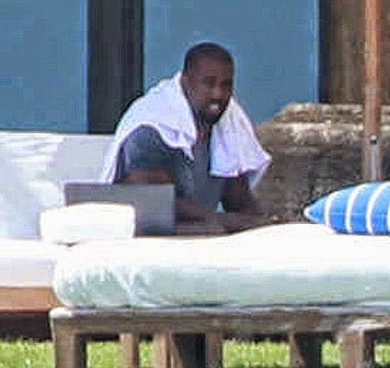 Kim Kardasian and Kanye West snuggle in a sun lounger as they enjoying the second anniversary trip in Punta Minta, Mexico on Tuesday, June 10, 2014.