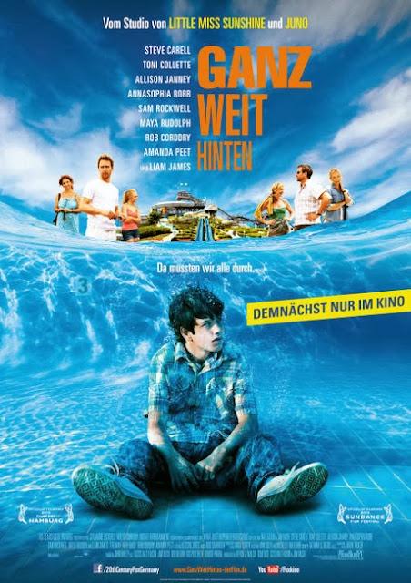 Duncan sitzt in Klamotten im Pool unter Wasser; An der Wasseroberfläche stehen seine Familie und seine Kollegen auf unterschiedlichen Seiten